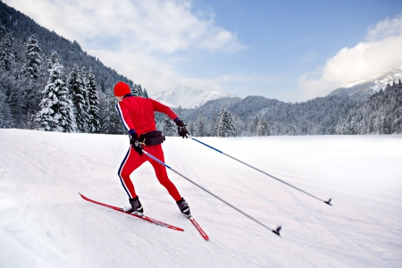 A man cross-country skiing in front of winter landscape photo
