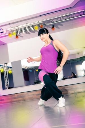 zumba: Mujer joven en traje de deporte en una aeróbica y zumba ejercicio