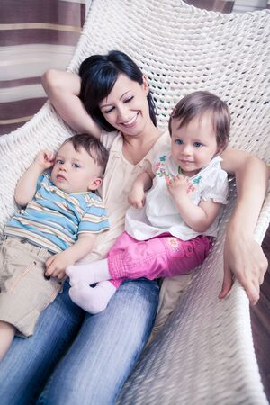 indoor portrait of a young woman with toddler twins in the living room photo