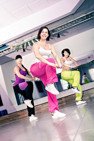 young women in sport dress at an aerobic and zumba exercise Фото со стока