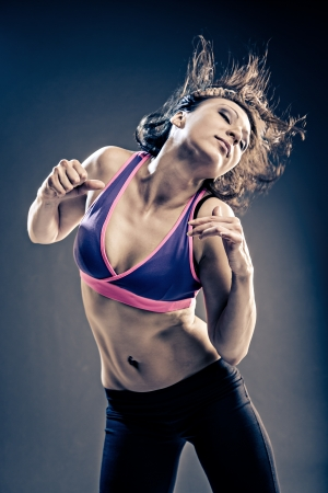 young woman in sport dress dancing in zumba or reggaeton or hiphop style Stock Photo