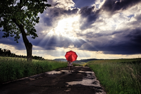 storm clouds: little girls walking on a road wit an umbrella Stock Photo
