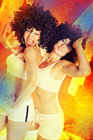two young women in sport dress dancing in zumba or reggaeton or hiphop style photo