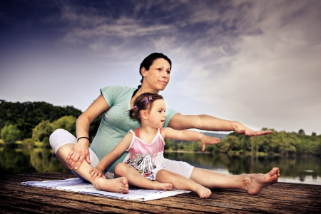 pregnant woman and her little daughter making yoga exercise at a lake 免版税图像