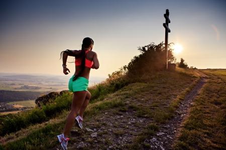mujeres corriendo: una mujer joven que se ejecutan en la monta�a Foto de archivo