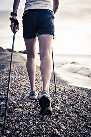 nordic walking: a woman hiking at the sea Stock Photo