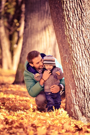 young father with a toddler in the autumn park photo