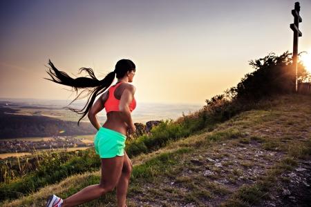 course � pied: une jeune femme marche dans les montagnes Banque d'images