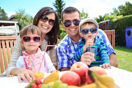 famiglia in giardino: giovane famiglia mangiare in giardino Archivio Fotografico
