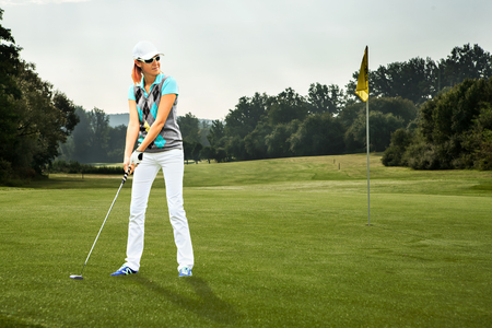 female golf player with a golf club on the course photo