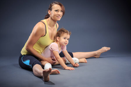 Studio shot of a little girl with mother at fitness exercise photo