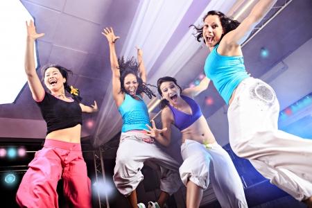 fitness training: jonge vrouwen in de sport jurk springen in een aërobe en zumba oefening