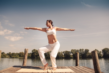 young woman making tai chi exercise at a lake