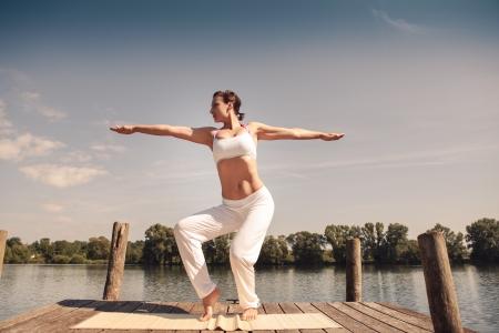 young woman making tai chi exercise at a lake Reklamní fotografie - 24212940