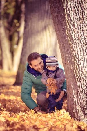 jeune père avec un bébé dans le parc en automne Banque d'images - 24347711