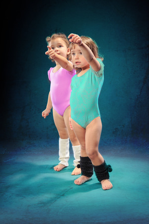 Studio shot of two little girls at fitness exercise photo