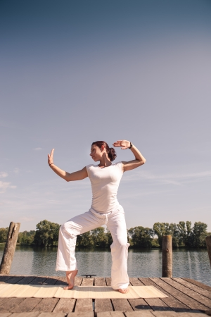 young woman making tai chi exercise at a lake photo