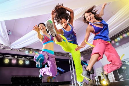 dance: young women in sport dress jumping at an aerobic and zumba exercise Stock Photo