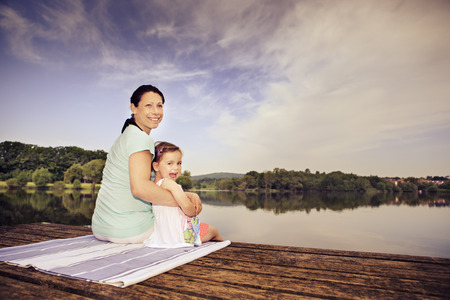 pregnant woman and her little daughter making yoga exercise at a lake. Lichtenfels, Germany photo