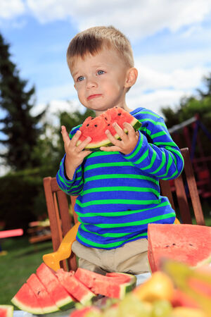 little boy eating a watermelon in the garden photo