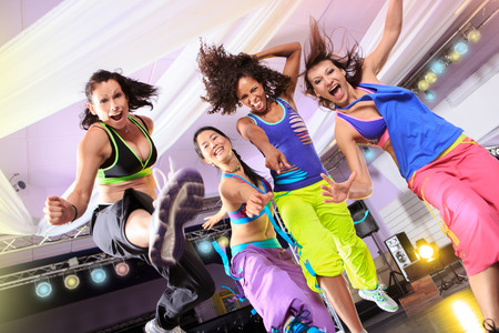 young women in sport dress jumping at an aerobic and zumba exercise photo