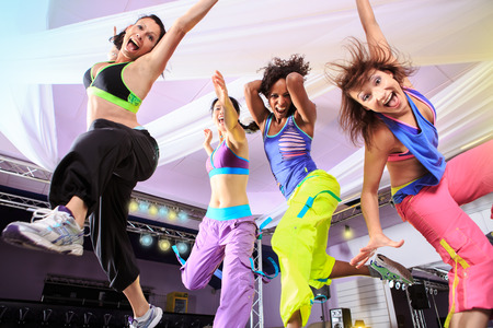 young women in sport dress jumping at an aerobic and zumba exercise Stock Photo