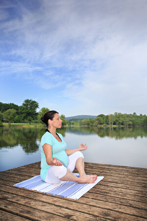 young pregnant woman making yoga exercise at a lake photo