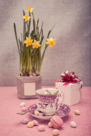 The easter installation with a cup, narcissi and sweets photo