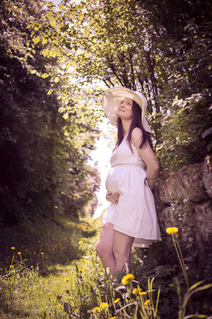 outdoor portrait of a young pregnant woman photo