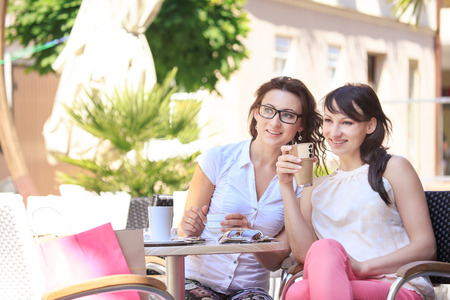 portrait of two young women in a street cafe photo