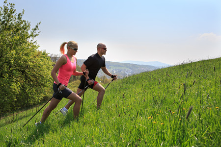 a couple making nordic walking training through rural landscape