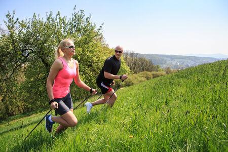 woman hiking: a couple making nordic walking training through rural landscape