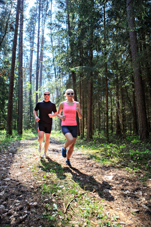 a couple jogging through the forest
