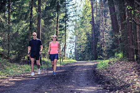 a couple making nordic walking training through forest