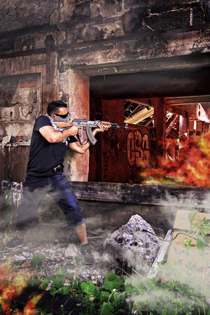 militant: masked militant with a submachine gun by running street battle