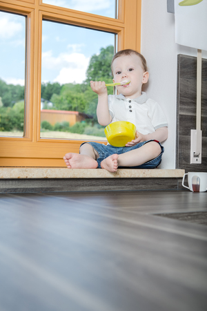 fmale: a 1,5 years old boy in the kitchen Stock Photo
