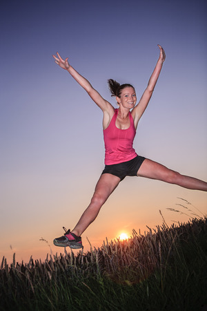 a young jumping woman in front of rural landscape and sunset photo