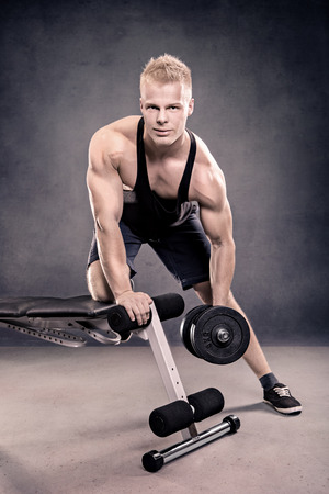 barbel: studio portrait of a young man in the bodybuilder pose Stock Photo