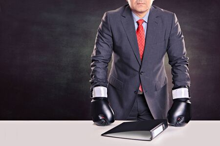 portrait of a male office worker with boxing gloves in the defensive stance Stock Photo