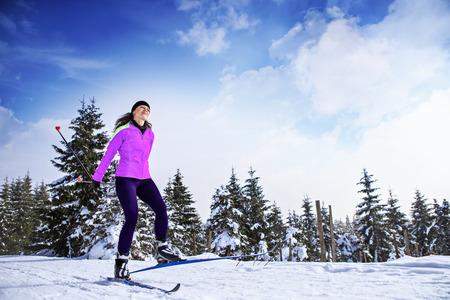 Een vrouw cross-country skiën in het winterse bos