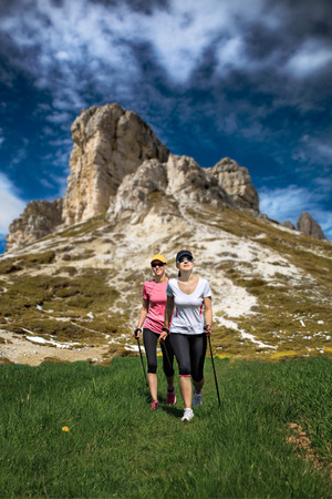 nordic walking: women nordic walking through mountains