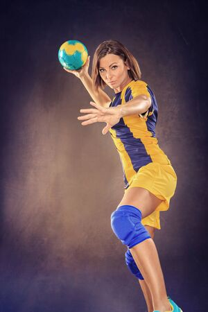 female handball player with a ball on the field