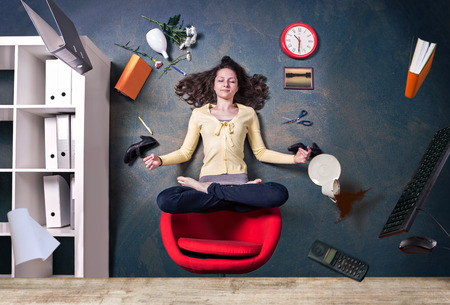young woman levitating by a yoga pose in the office