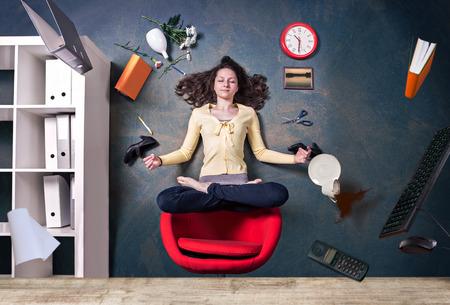 mujer joven levitando por una pose de yoga en la oficina Foto de archivo