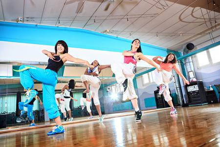 grupo de mujeres en traje de deporte en el ejercicio de la danza de la aptitud o aeróbic