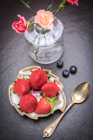 pinks: strawberries and a vase with pinks in rural style