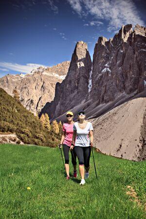 nordic walking: women nordic walking through rural landscape