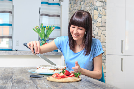 strawberies: woman baking a pie with strawberies at home