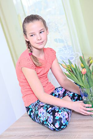 portrait of a teenage girl with flowers at home Stock Photo