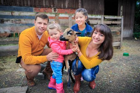 granja: una familia de granjeros con una oveja delante de la finca Foto de archivo